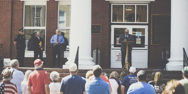 Pastor Perry Cleek speaks during an Independence Day ceremony honoring local law enforcement at the Washington County Court House in Jonesborough, Tenn., on July 4, 2020. Public Safety Director Craig Ford; Rodney Metcalf, chairman of the deacons at Lighthouse Missionary Baptist Church; and Police Chief Ron Street are pictured on the left.