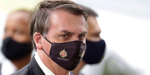 In this May 18, 2020, file photo, Brazilian President Jair Bolsonaro wears a mask due to the coronavirus pandemic as he talks with supporters upon departure from his official residence, Alvorada palace, in Brasilia, Brazil.