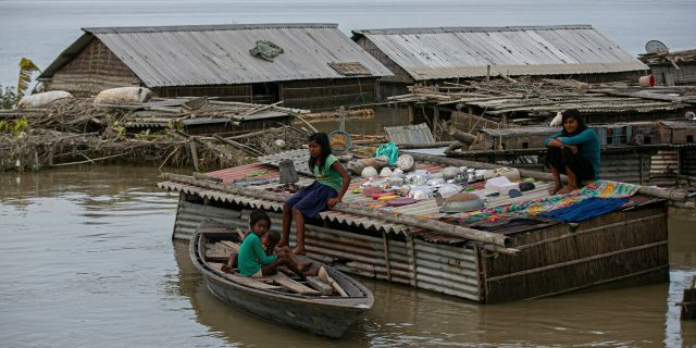 A flood affected family takes shelter on the roof of their submerged house along river Brahmaputra in Morigaon district, Assam, India, July 16.