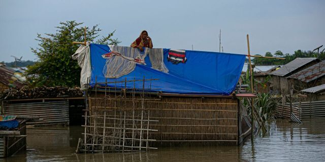 A flood affected Indian woman stands on the roof of her partially submerged house along river Brahmaputra in Morigaon district, Assam, India, July 16.