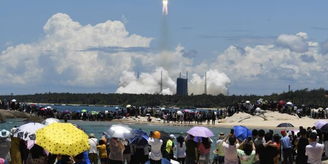 Spectators watch as a Long March-5 rocket carrying the Tianwen-1 Mars probe lifts off from the Wenchang Space Launch Center in southern China's Hainan Province, Thursday, July 23, 2020. China launched its most ambitious Mars mission yet on Thursday in a bold attempt to join the United States in successfully landing a spacecraft on the red planet. (Yang Guanyu/Xinhua via AP)