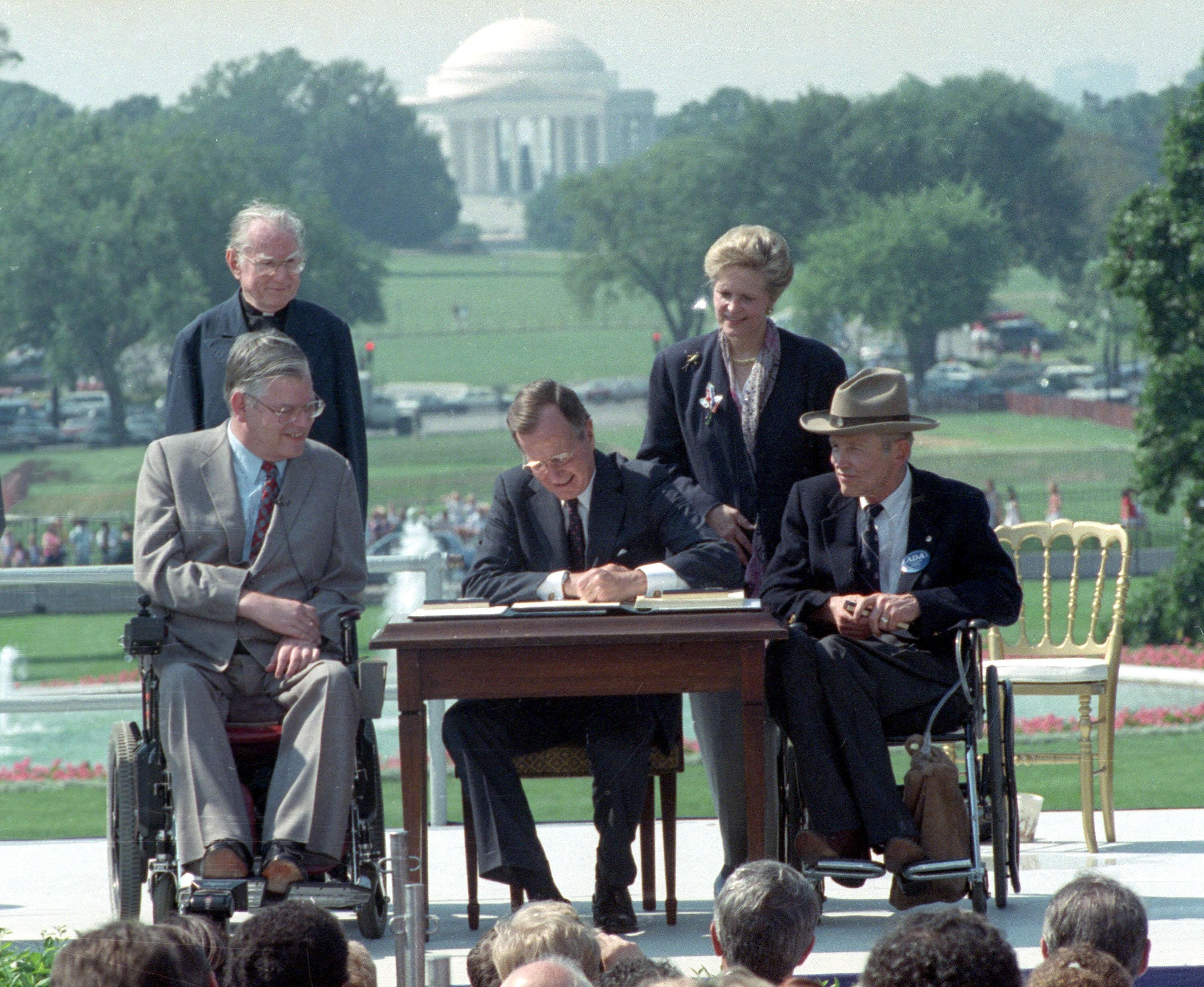 President George H.W. Bush signs the Americans With Disabilities Act on the South Lawn of the White House on July 26, 1990. W