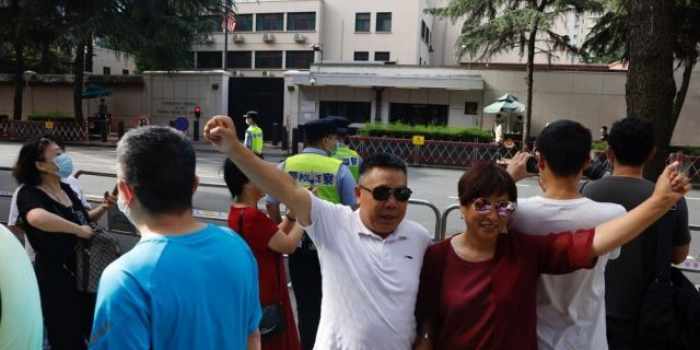 Residents raise their fists to pose for a photo outside the United States Consulate in Chengdu in southwest China's Sichuan province on Sunday, July 26, 2020. China ordered the United States on Friday to close its consulate in the western city of Chengdu, ratcheting up a diplomatic conflict at a time when relations have sunk to their lowest level in decades.
