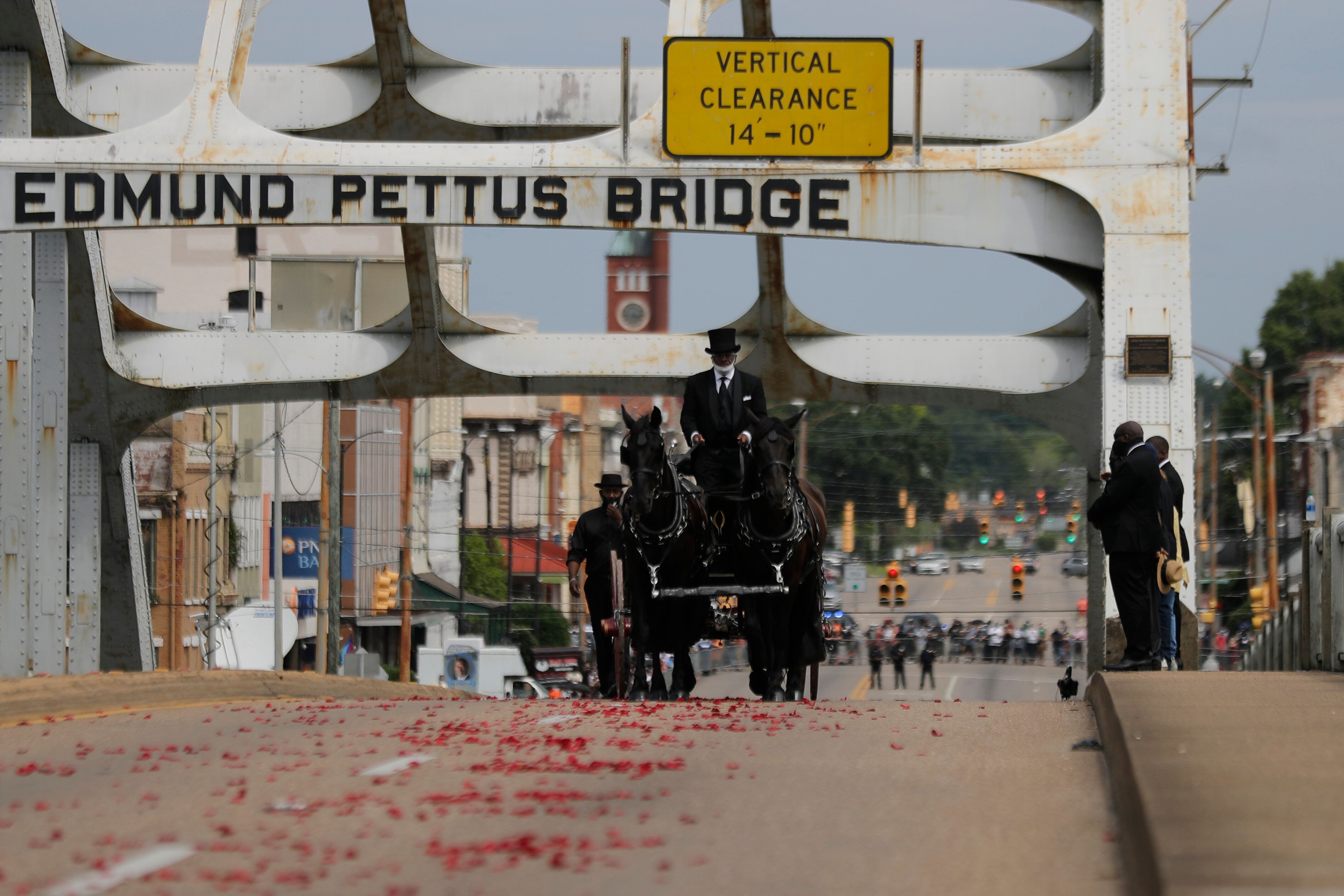 The casket of Rep. John Lewis moves over the Edmund Pettus Bridge by horse-drawn carriage during a memorial service for Lewis