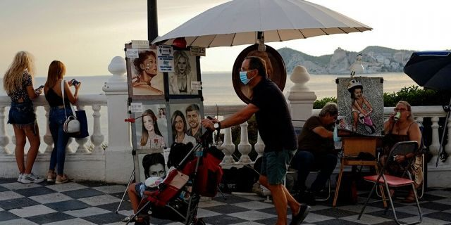 A tourist pushes a stroller as illustrators wait for customers, in Benidorm, south-east Spain, Monday, July 27, 2020. (AP Photo/Alvaro Barrientos)