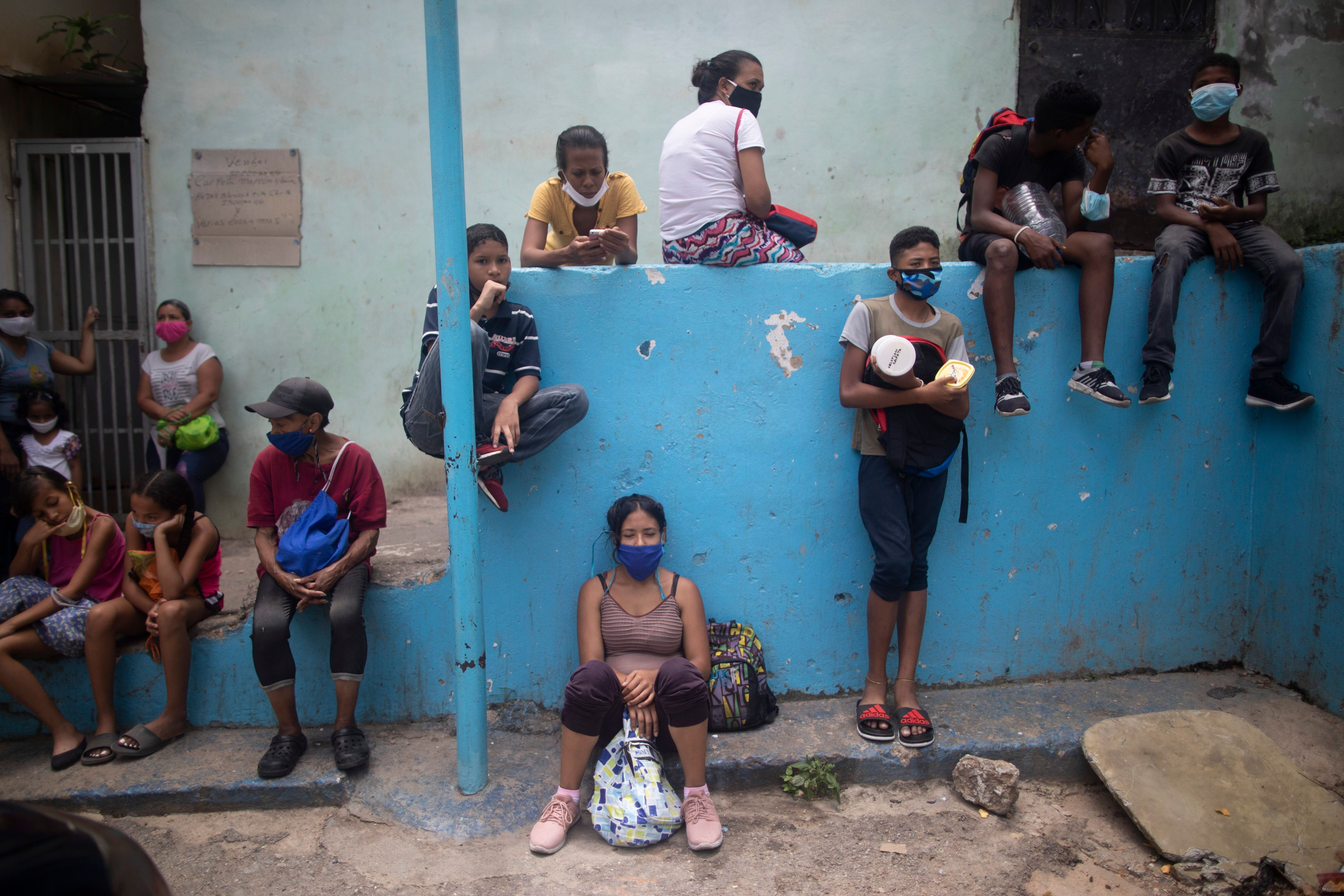 Residents wearing protective face masks wait outside a soup kitchen to receive pack-and-go lunches in the Petare neighborhood