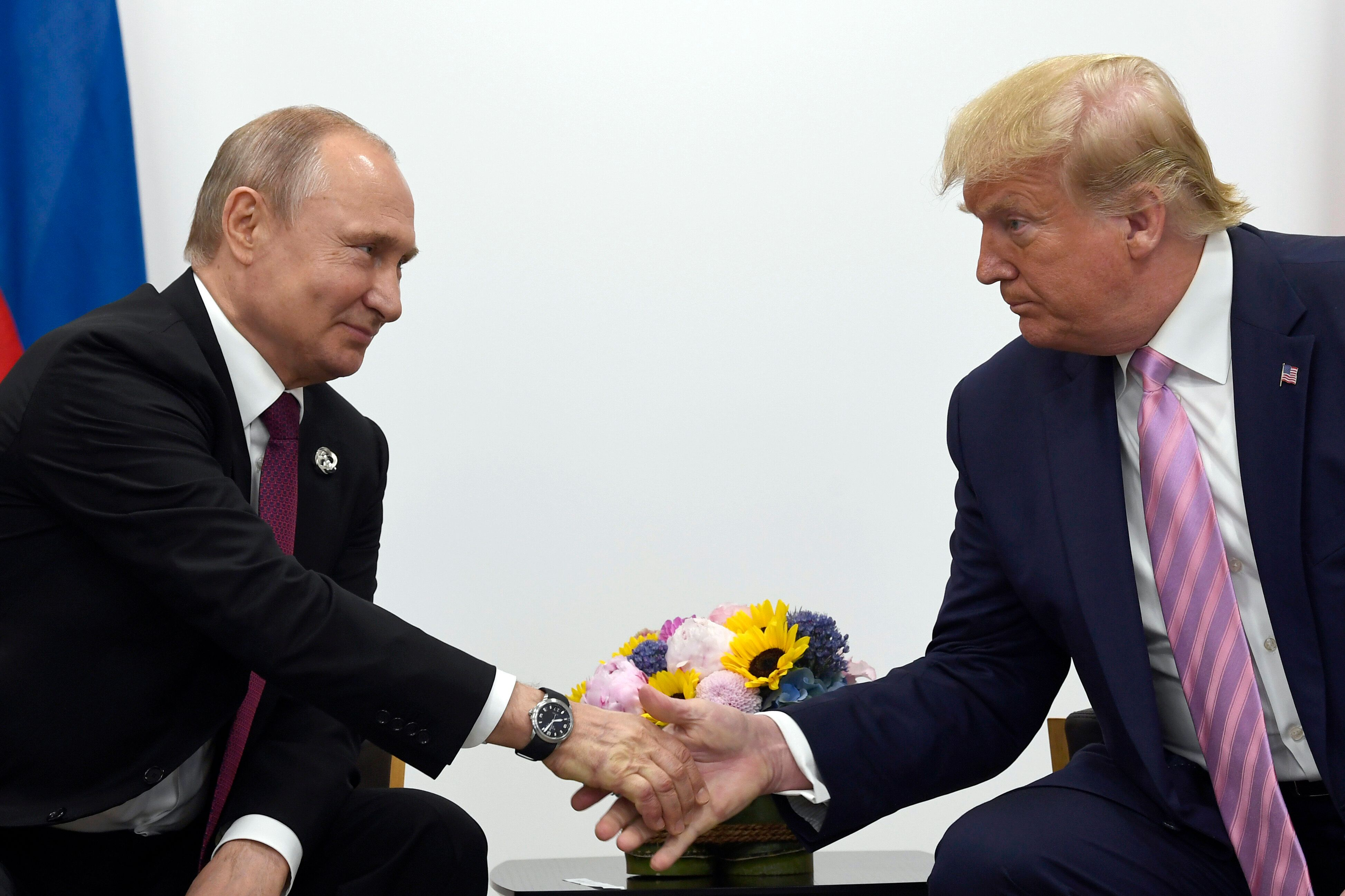 President Donald Trump, right, shakes hands with Russian President Vladimir Putin, left, during a bilateral meeting on the si