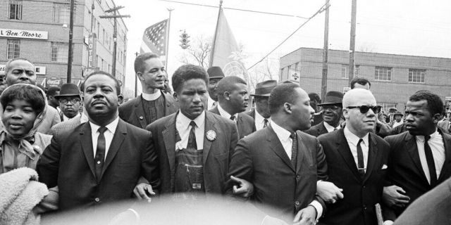 In this March 17, 1965, file photo, Dr. Martin Luther King Jr., fourth from left, foreground, locks arms with his aides as he leads a march of several thousand to the courthouse in Montgomery, Ala. From left are: an unidentified woman, Rev. Ralph Abernathy, James Foreman, King, Jesse Douglas Sr., and John Lewis. Lewis, who carried the struggle against racial discrimination from Southern battlegrounds of the 1960s to the halls of Congress, died Friday, July 17, 2020. (AP Photo/File)