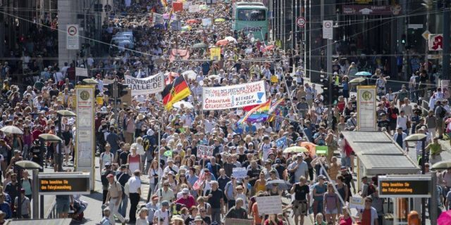 """Thousands march along the 'Friedrichstrasse' during the demonstration against corona measures in Berlin, Germany, Saturday, Aug. 1, 2020. The initiative """"Querdenken 711"""" has called for this. The motto of the demonstration is """"The end of the pandemic - Freedom Day""""."""