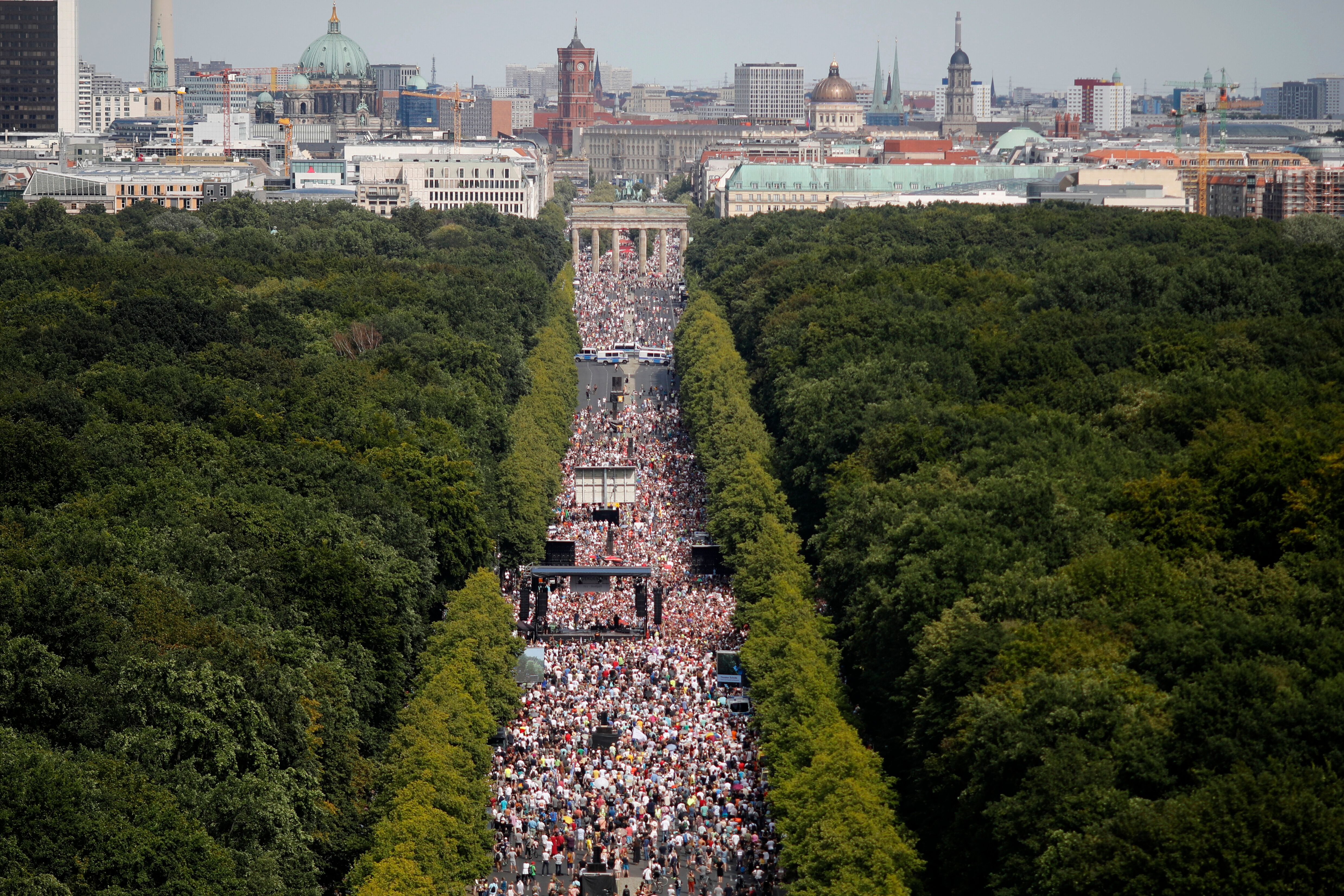 People gather at the Brandenburg gate for a demonstration against coronavirus restrictions in Berlin, Germany, Saturday, Aug.