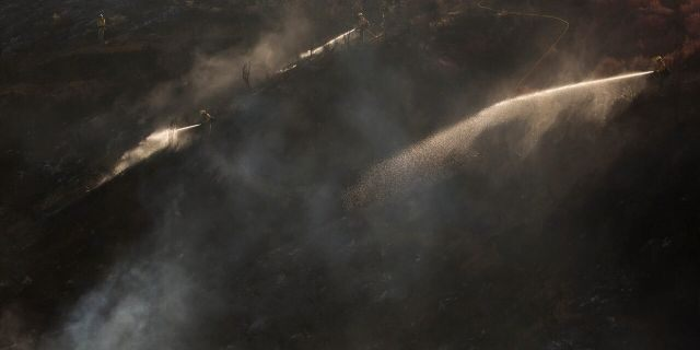 Hand crews work on the remaining hot spots from a brush fire at the Apple Fire in Cherry Valley, Calif., Saturday, Aug. 1, 2020.