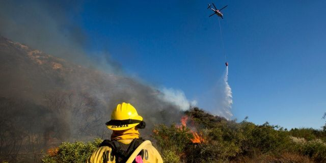 A firefighter watches as a helicopter drops water onto the Apple Fire near Banning, Calif., Sunday, Aug. 2, 2020.