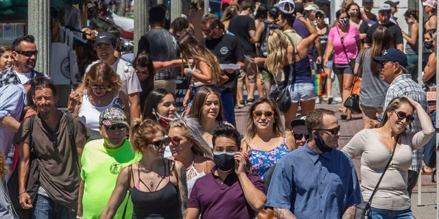 People cross the street in Huntington Beach, California, on July 19, 2020 amid the coronavirus pandemic. (Photo by APU GOMES/AFP via Getty Images)