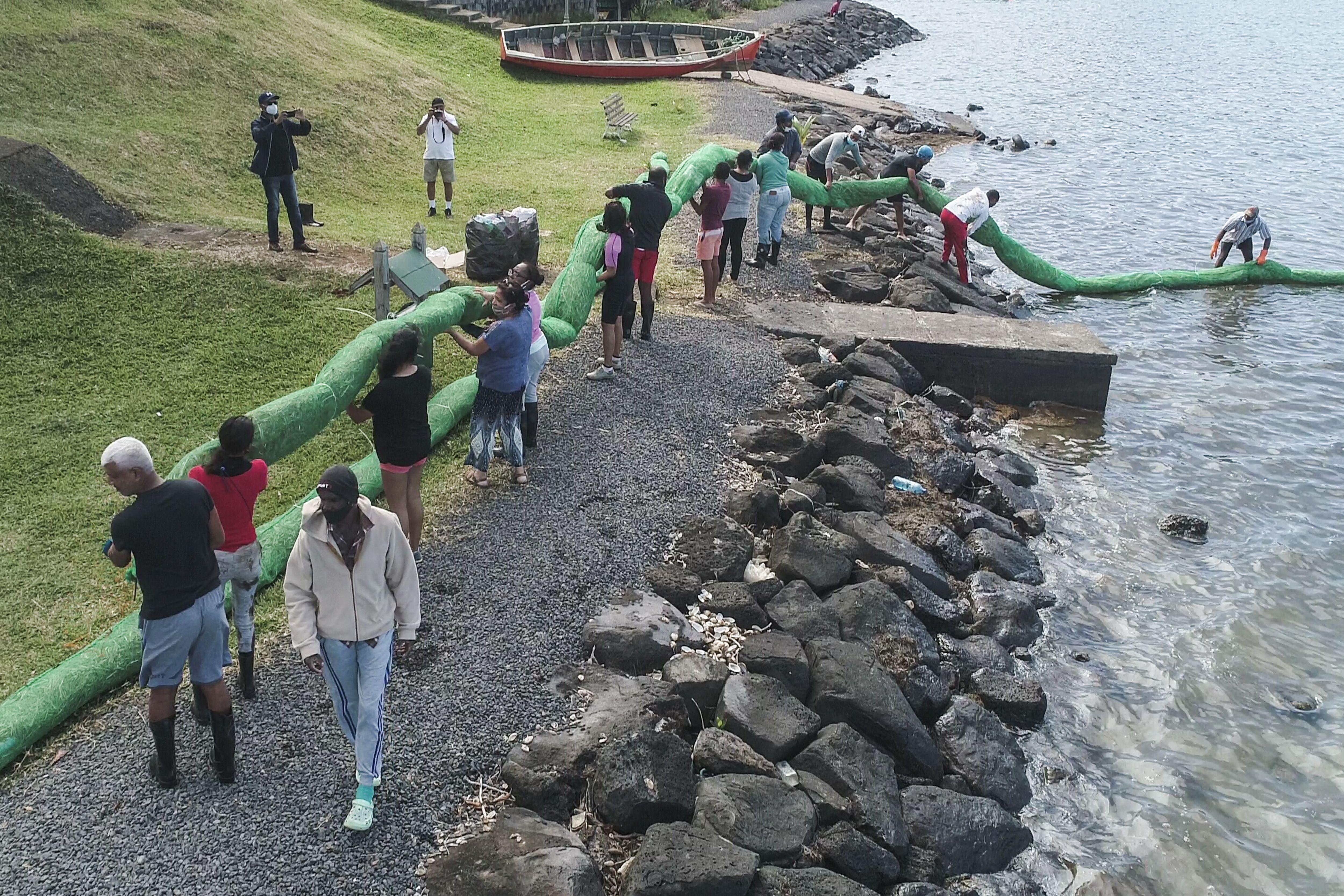 Volunteers carry the handmade oil barrier to block leaked oil from the MV Wakashio bulk carrier.