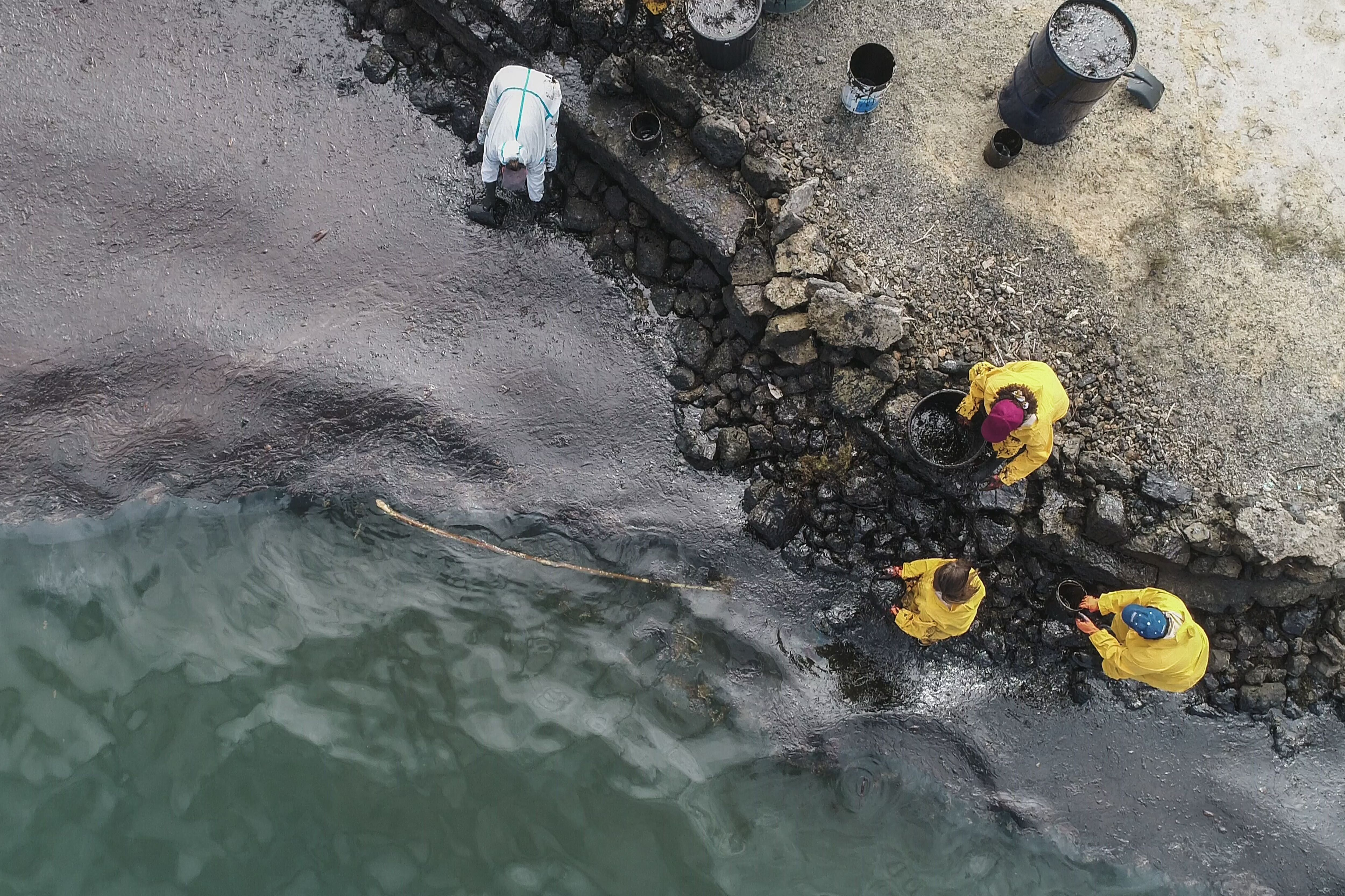 People scoop leaked oil from the MV Wakashio bulk carrier.
