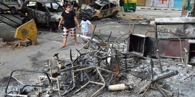 A woman and child walk past the wreckage of vehicles and furniture burnt during violent protests in Bengaluru, India, on Wednesday, Aug. 12, 2020. (AP Photo)