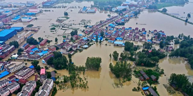 This July 20, 2020, aerial file photo released by Xinhua News Agency shows the extent of flooding in Guzhen Town of Lu'an City in eastern China's Anhui Province.