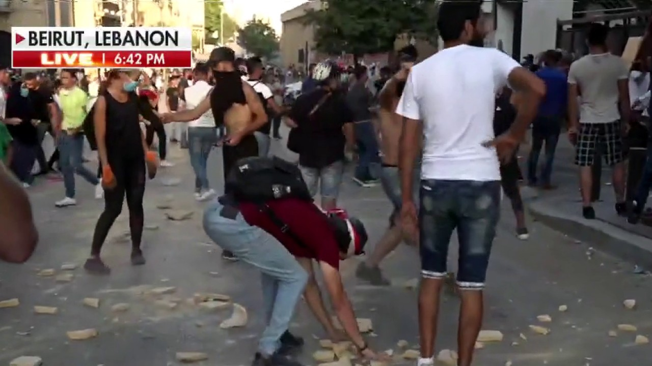 Lebanese protesters clash with police in Beirut after prime minister announces resignation