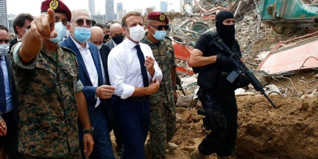 French President Emmanuel Macron, center, visits the site of the explosion at the port of Beirut, Lebanon on Thursday, Aug. 6. (AP Photo/Thibault Camus, Pool)