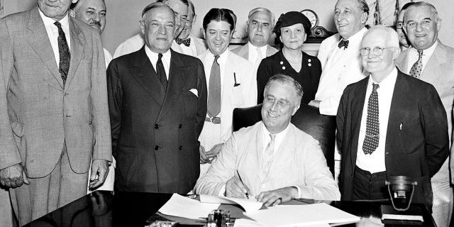 President Franklin Roosevelt signs the Social Security Bill in Washington on Aug. 14, 1935. (AP Photo)