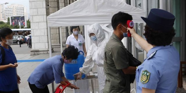 People disinfect their hands and have their temperatures taken before going into the Pyongyang Railway Station in Pyongyang, North Korea, Thursday, Aug. 13, 2020. (AP Photo/Cha Song Ho)