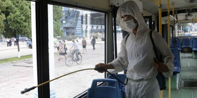 A man in a protective suit disinfects the inside of a trolley bus to help curb the spread of the coronavirus in Pyongyang, North Korea, Thursday, Aug. 13, 2020. (AP Photo/Jon Chol Jin)