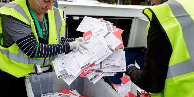 King County Election workers collect ballots from a drop box in the Washington State primary on Tuesday, March 10, 2020, in Seattle. (AP Photo/John Froschauer)