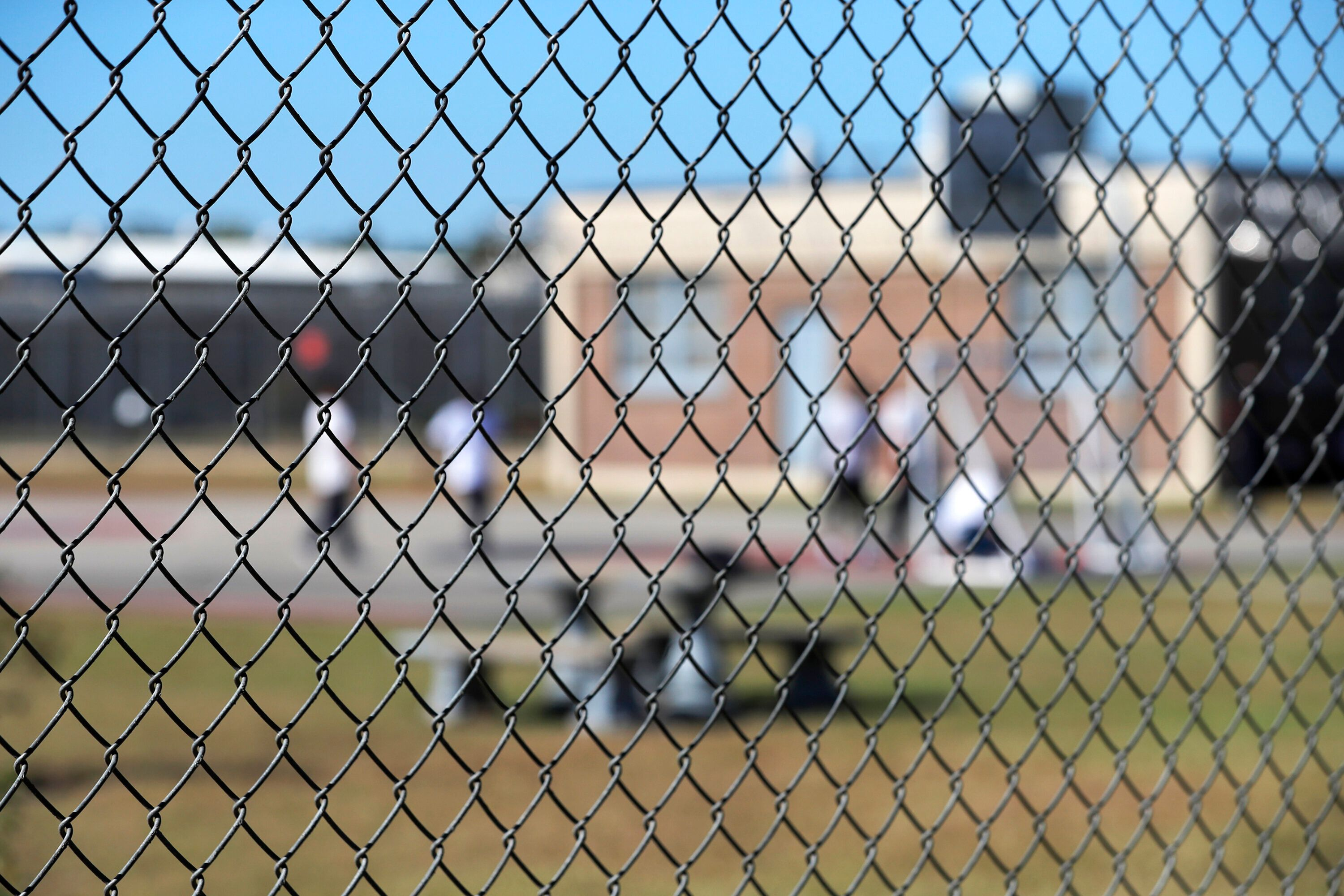 In this Sept. 26, 2019, file photo, detainees sit in a yard during a media tour inside the Winn Correctional Center in Winnfi