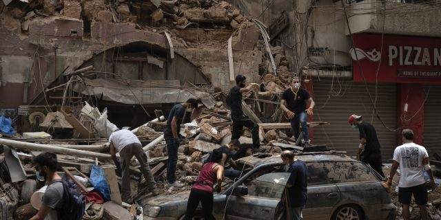 People remove debris from a house damaged by Tuesday's explosion in the seaport of Beirut, Lebanon, on Aug. 7. (AP)