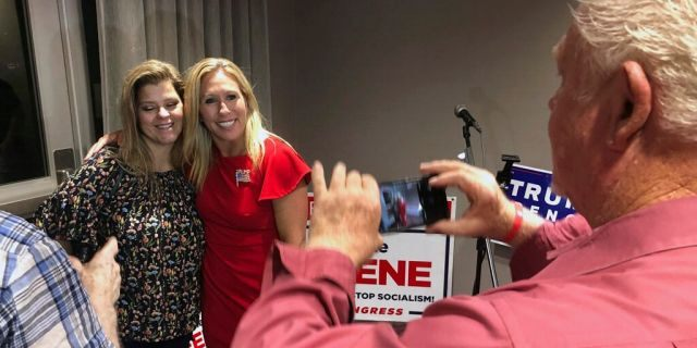 Supporters take photos with construction executive Marjorie Taylor Greene, background right, late Tuesday, Aug. 11, 2020, in Rome, Ga. Greene won the GOP nomination for northwest Georgia's 14th Congressional District. (AP Photo/Mike Stewart)