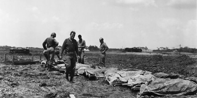 """FILE - In this B/W file photo dated May 9, 1945, while American cities were going wild on an unconfirmed report of Germany's unconditional surrender, American soldiers and marines are checking the identification of their dead on May 9, 1945, on Okinawa, Japan. Resistance continues to be savage on this island in Japan's front yard. Following the defeat of the Nazis on May 8, 1945, Allied troops carried on fighting until Japan's surrender, but many of them felt their efforts had not been fully recognized and dubbed themselves the """"forgotten army.""""(AP Photo/Sam Goldstein, FILE)"""