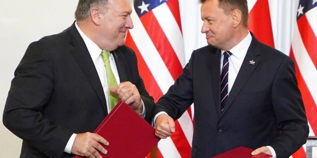 US Secretary of State Mike Pompeo, left, and Poland's Minister of Defence Mariusz Blaszczak greet each other after signing the US-Poland Enhanced Defence Cooperation Agreement in the Presidential Palace in Warsaw, Poland, Saturday Aug. 15, 2020. (Janek Skarzynski/Pool via AP)