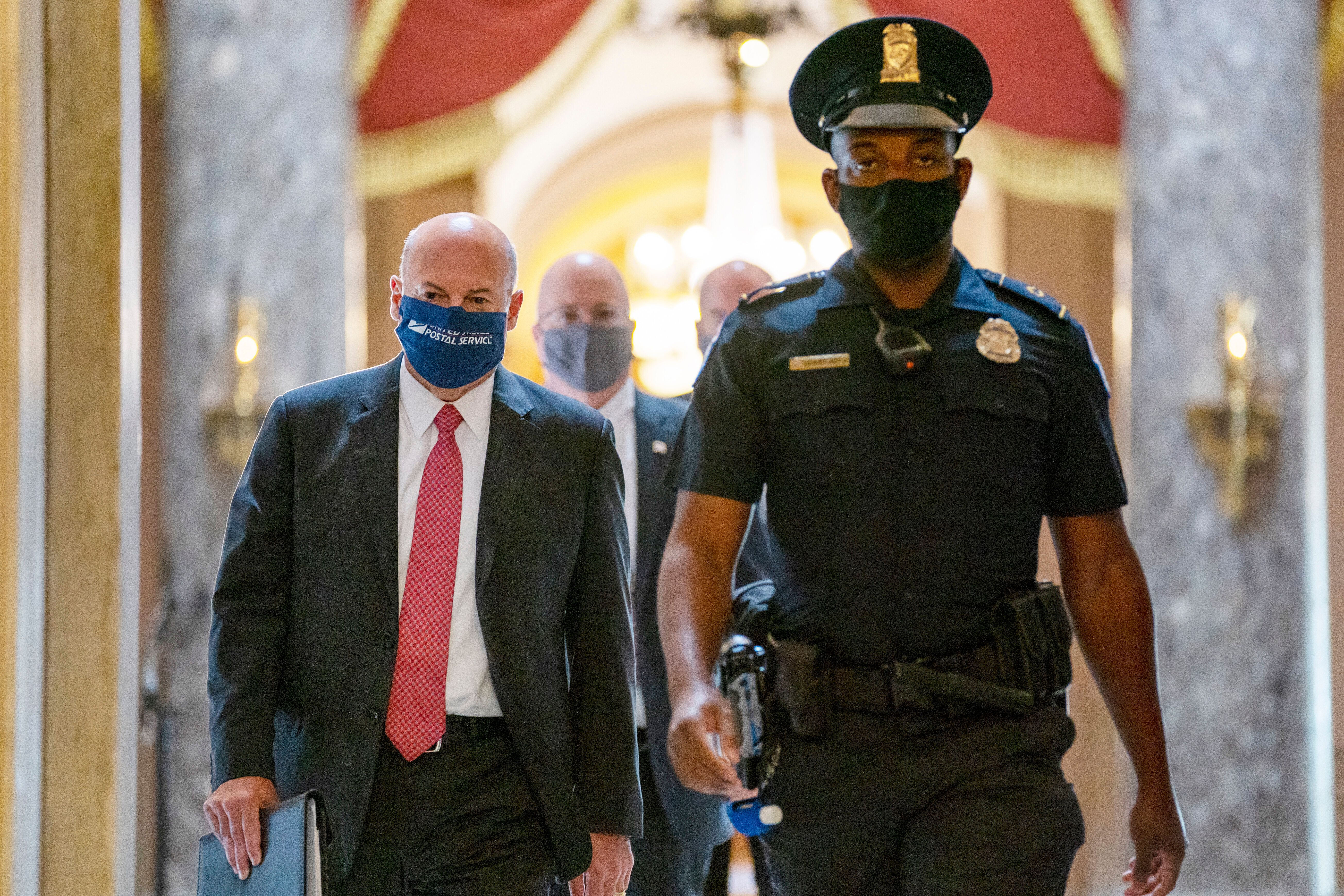 In this Aug. 5, 2020, file photo Postmaster General Louis DeJoy, left, is escorted to House Speaker Nancy Pelosi's office on