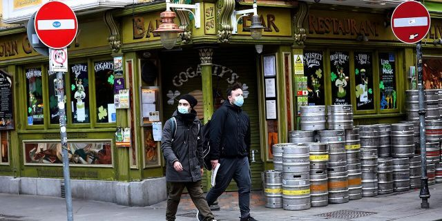 Tourists wearing face masks walk past a closed pub in Dublin city center on March 16. (AP Photo/Peter Morrison, File)