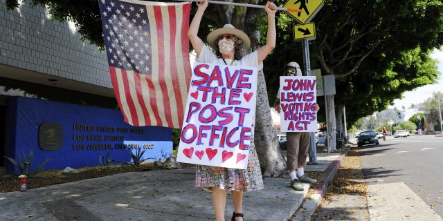 Erica Koesler, left, and David Haerle, both of Los Angeles, demonstrate outside a USPS post office, Saturday, Aug. 15, 2020, in the Los Feliz section of Los Angeles. (AP Photo/Chris Pizzello)