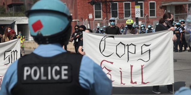 Police stand guard as pro and anti-police demonstrators gather outside of the Homan Square police station on August 15, 2020 in Chicago, Illinois.