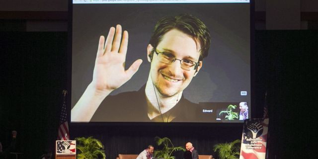 In this Feb. 14, 2015, file photo, Edward Snowden appears on a live video feed broadcast from Moscow at an event sponsored by ACLU Hawaii in Honolulu. This photo predates the speaking engagements reported by APD in its recent court filing. (AP Photo/Marco Garcia, File)