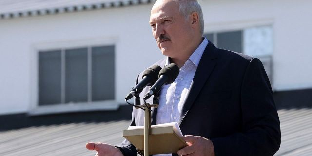Belarusian President Alexander Lukashenko addresses workers of the Minsk Wheel Tractor Plant in Minsk, Belarus, on Monday. Several thousand factory workers have taken to the streets of Minsk demanding the resignation of authoritarian Belarusian President Alexander Lukashenko. (Nikolai Petrov/BelTA Pool Photo via AP)