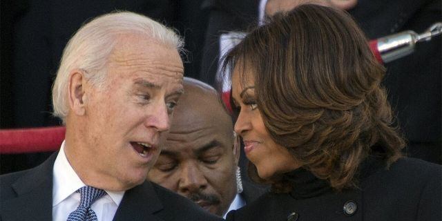 Michelle Obama and Joe Biden chat during a Veteran's Day ceremony at Arlington National Cemetery in 2013. (JIM WATSON/AFP via Getty Images)