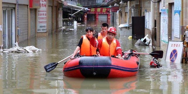 Rescuers use an inflatable boat as they evacuate people from a flooded neighborhood in Neijiang in southwestern China's Sichuan Province, Tuesday, Aug. 18, 2020.
