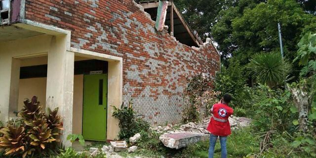 In this handout photo provided by the Philippine Red Cross, a volunteer takes photos of a damaged structure after a strong earthquake struck in Cataingan, Masbate province, central Philippines on Tuesday Aug. 18, 2020.