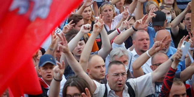 Belarusian opposition supporters shout slogans during a protest rally in front of the government building at Independent Square in Minsk, Belarus, Tuesday, Aug. 18, 2020.
