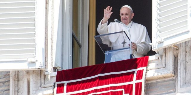 Pope Francis waves from his studio window overlooking St. Peter's Square at the Vatican on Sunday, July 5, 2020. (AP Photo/Riccardo De Luca)
