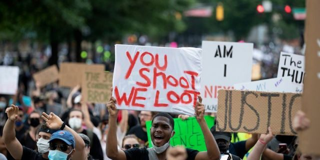 People carry signs as they march Monday, June 1, 2020, in Atlanta during demonstration over the death of George Floyd, who died after being restrained by Minneapolis police officers on May 25. (AP Photo/John Bazemore).