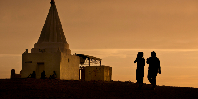 The sun sets as women visit a Yazidi shrine overlooking at Kankhe Camp for the internally displaced in Dahuk, northern Iraq, in this Wednesday, May 18, 2016 file photo. Over the past centuries, the Yazidi community, one of Iraq's oldest religious minorities, has repeatedly been subjected to brutal attacks leaving thousands of its members dead. One of their worst subjugations occurred four years ago with the rise of the extremist Islamic State group.