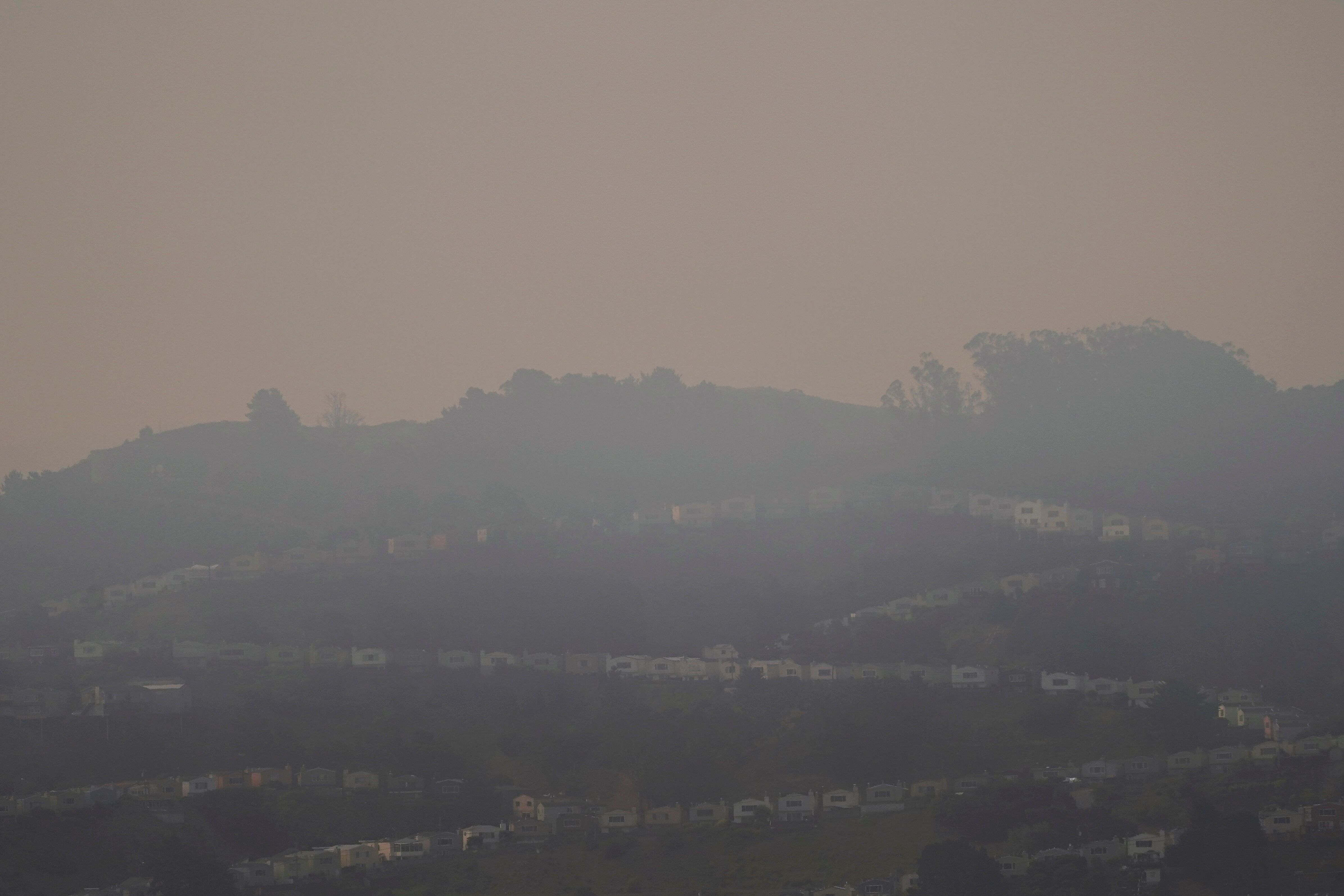 Smoke from wildfires hangs over homes in San Francisco, Wednesday, Aug. 19, 2020. (AP Photo/Jeff Chiu)