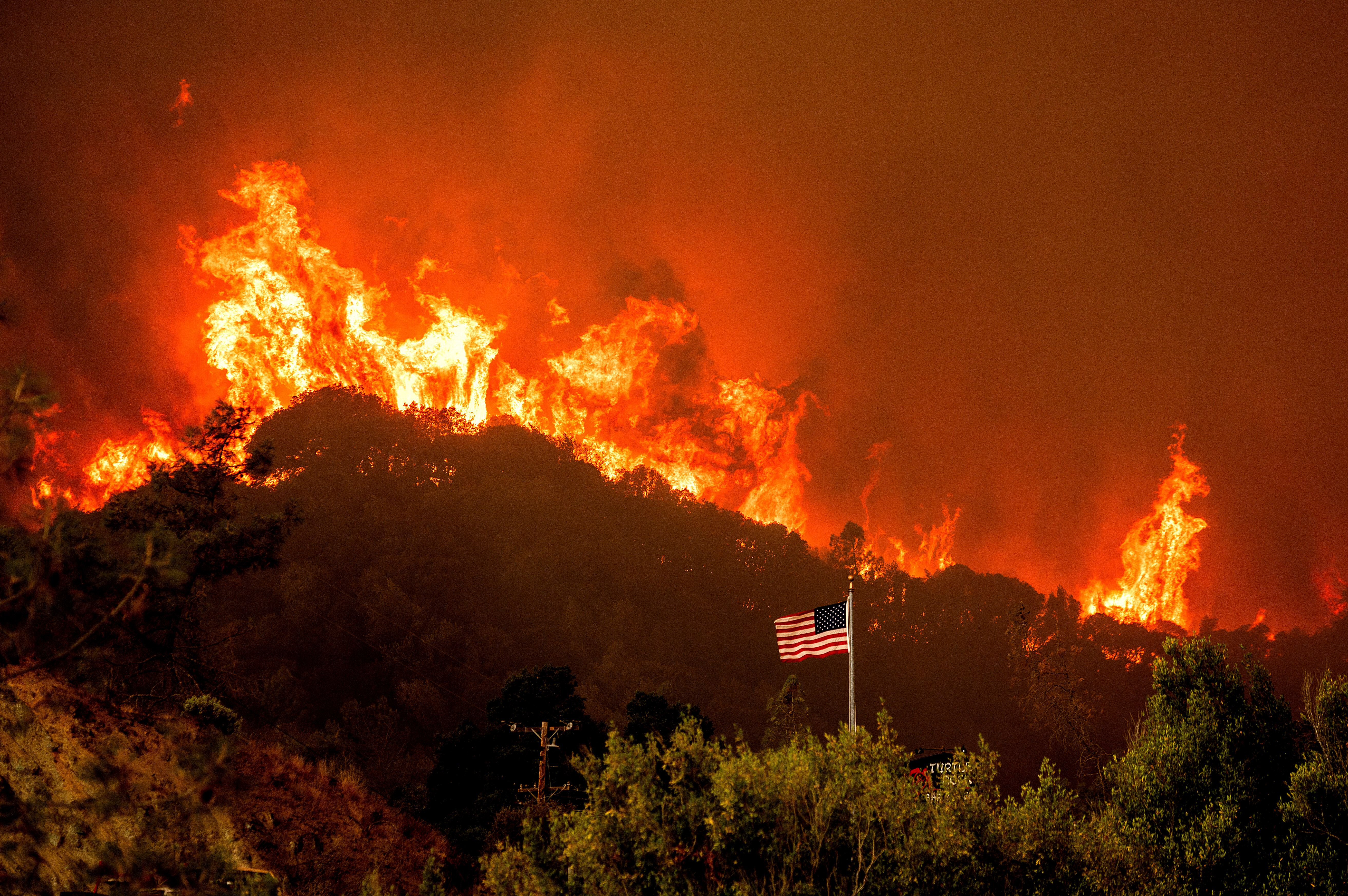 A flag flies as flames from the LNU Lightning Complex fires crest a ridge Tuesday, Aug. 18, 2020, in Napa County, Calif. (AP