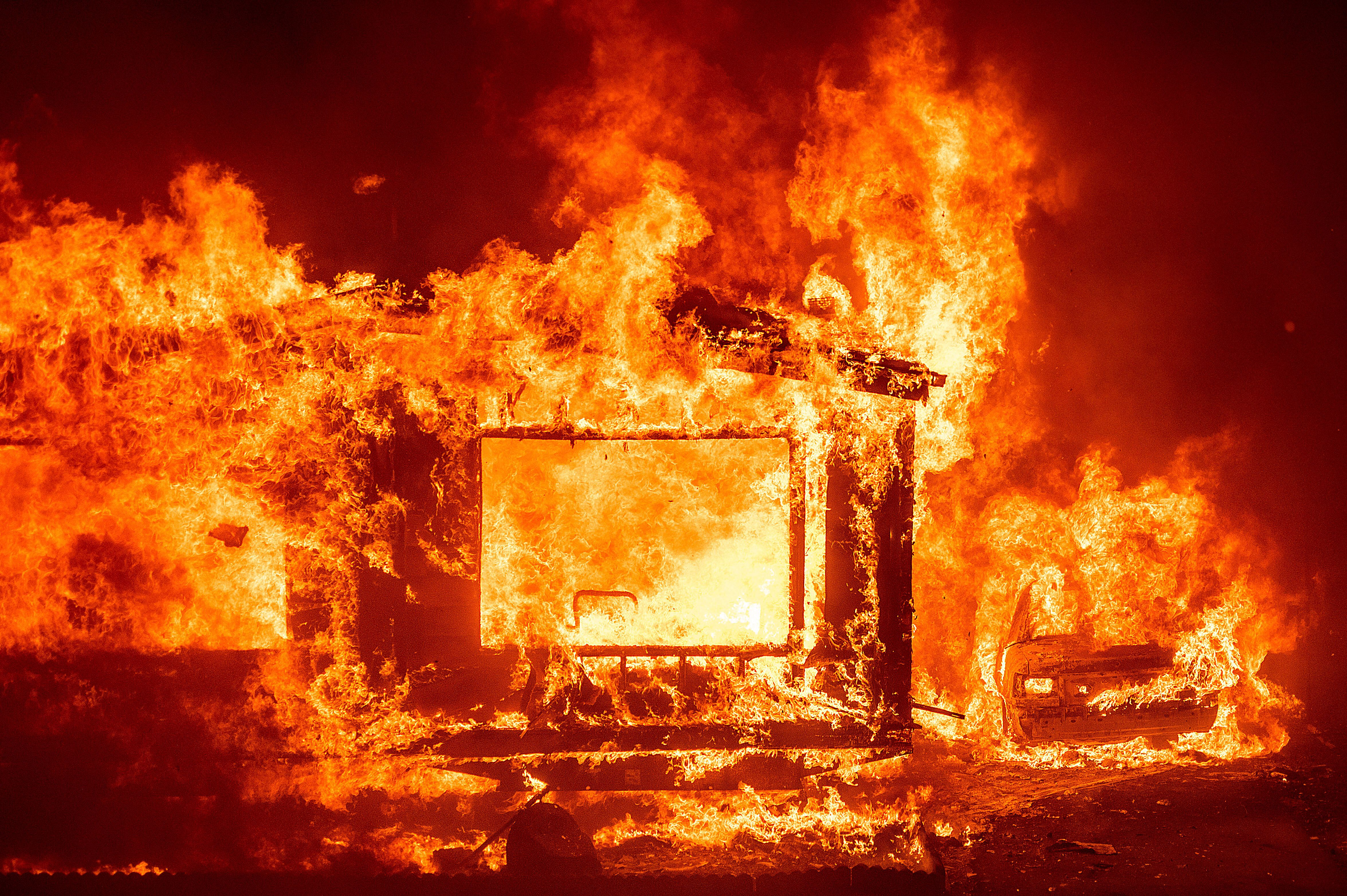 A mobile home and car burn at Spanish Flat Mobile Villa as the LNU Lightning Complex fires tear through unincorporated Napa C
