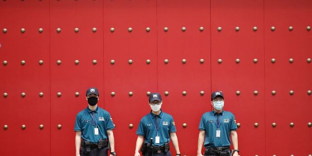 Police officers wearing face masks to help protect against the spread of the new coronavirus, stand guard in downtown Seoul, South Korea, Tuesday, Aug. 4, 2020. (AP Photo/Lee Jin-man)
