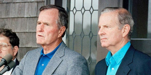Then-Secretary of State James Baker III, right, joins President George H. W. Bush in addressing reporters at Kennebunkport, Maine,Aug. 11, 1990. (Associated Press)